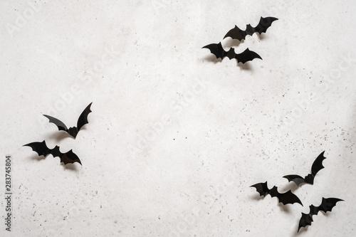 halloween decoration concept - black bats on white concrete background