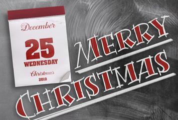 words Merry Christmas on chalkboard with tear-off calendar on December 25