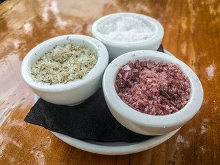 3 different types os salt on small white containers.