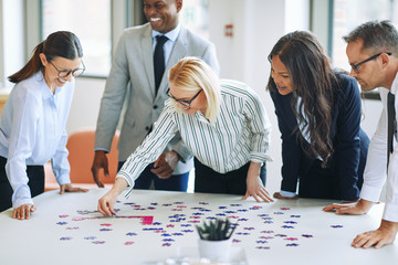Laughing businesspeople trying to solve a puzzle in an office