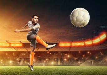 Soccer player kicks a ball. Night illuminated soccer stadium with dramatic sky