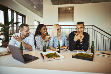 Group of laughing coworkers having pizza and beer after work