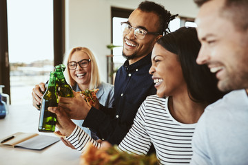 Diverse businesspeople laughing and cheering with beers while ea