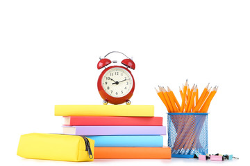 School supplies with red alarm clock on white background