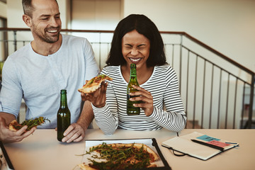Laughing African American businesswoman having pizza and beers a