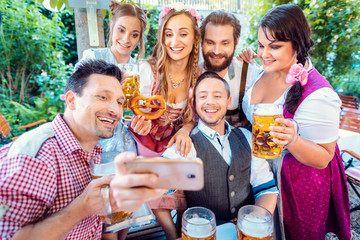 Cheerful group of friends taking a selfie in Bavarian beer garden