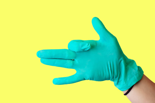 Female hand in blue latex glove makes a gesture resembling a dog with open mouth isolate a light yellow background. Medical health concept.