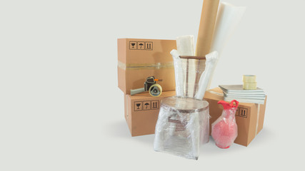 Moving scene with a chair and vase packed in plastic bubble with closed cardboard boxes and rolls of plastic and foam to pack on white background