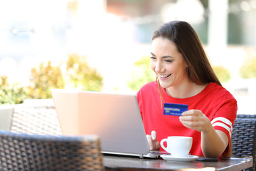 Happy teen paying online using a laptop and credit card