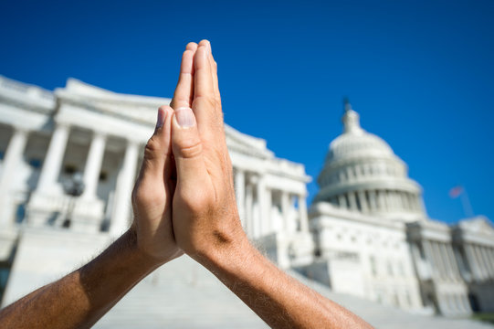 Hands held together in prayer in front on Capitol Building in Washington DC, USA