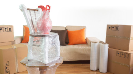 Moving scene with a vase on a chair on a table packed in plastic inside a room with a sofa, plastic rolls and closed cardboard boxes on white background