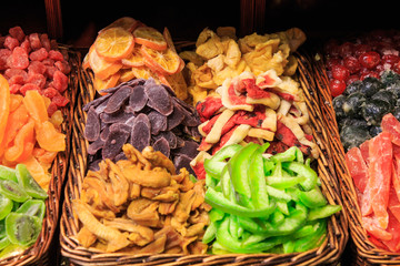 Different types of caramelized and dried fruits on a tray in the Boqueria market