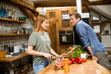 Beautiful young couple smiling while cooking in kitchen at home