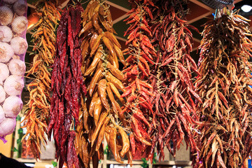 Different strips of hot peppers and chili peppers hanging from the ceiling in the Boqueria market