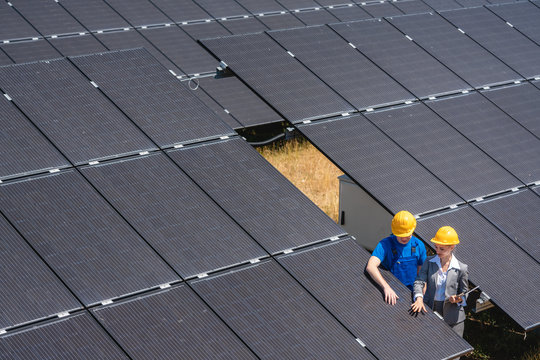 Two people standing amid solar cells in a power plant