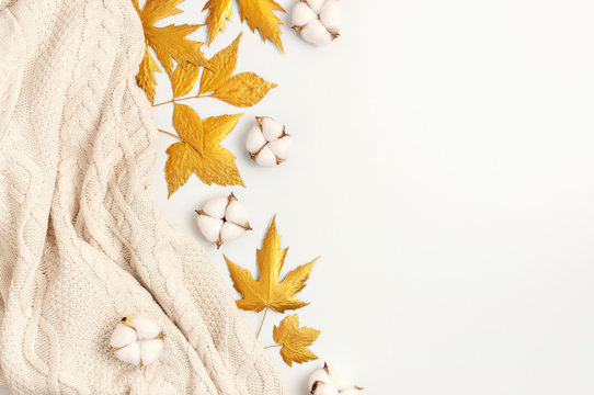 Flat lay autumn composition. Knitted woolen light beige sweater or plaid, golden dry leaves, cotton flowers on white background top view copy space. Autumn, fall concept