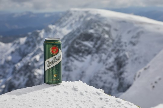 DUMBIER, SLOVAKIA - CIRCA 2017: A can of Zlaty Bazant Slovakian beer on a snowy moutntain top in the low tatras