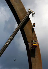A worker suspended from a crane brazes the last piece of the Arc Majeur, a 60-meter arch designed by French artist Bernar Venet and installed on the E411 highway in Lavaux-Sainte-Anne