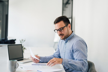Happy young businessman looking at papers graphs and charts using laptop at his office desk