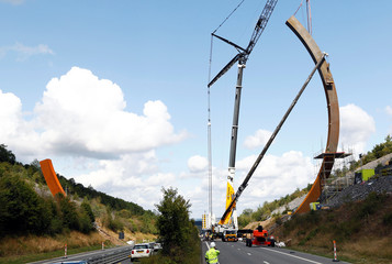 A crane is used to put the last piece of the Arc Majeur, a 60-meter arch designed by French artist Bernar Venet and installed on the E411 highway in Lavaux-Sainte-Anne