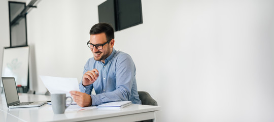 Young smiling cheerful confident businessman checking working plan and schedule or timetable in office copy space