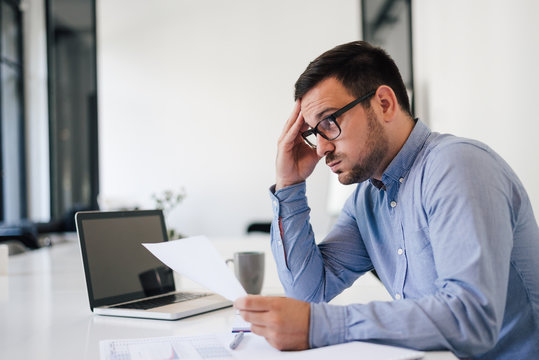 Stressed out and worried overworked businessman in office working under pressure and tight deadline