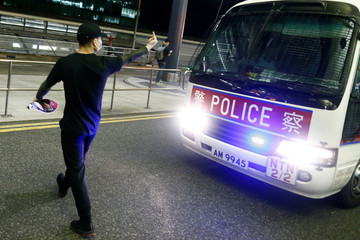 An anti-government protester gestures at a police van during clashes at the airport in Hong Kong