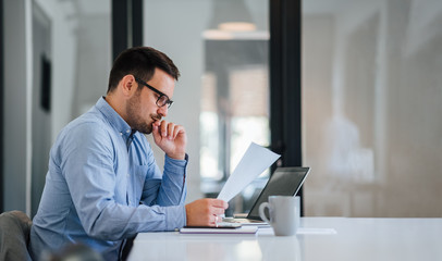 Serious pensive thoughtful young businessman or entrepreneur in modern contemporary office looking...