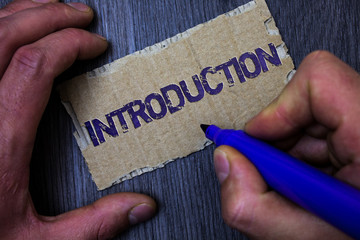 Text sign showing Introduction. Conceptual photo First part of a document Formal presentation to an audience Man working holding blue marker ideas message paperboard wooden background