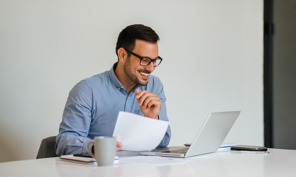 Young smiling cheerful businessman in office on video conference call