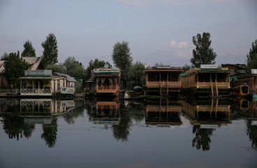 A Kashmiri woman rows her boat past houseboats in Dale Lake during restrictions after the scrapping of the special constitutional status for Kashmir by the government, in Srinagar