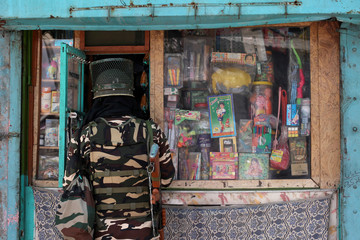 An Indian security force personnel buys goods from a shop during restrictions after the scrapping of the special constitutional status for Kashmir by the government, in Srinagar