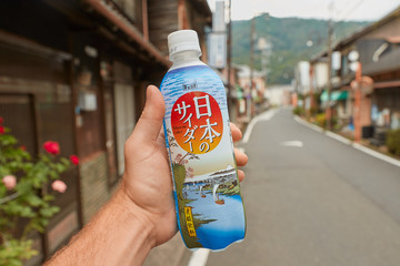 KASAGI, JAPAN - SEPTEMBER 8, 2018: Japanese soft drink Nihon No Cider held in hand in a village street. Vending machines all across the streets of Japan sell a wide variety of drinks.