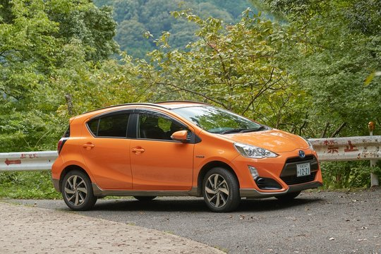 KASAGI, JAPAN - SEPTEMBER 16, 2018: Toyota Aqua compact car on a mountain road. Also known as Prius C outside of Japan, One of the most fuel efficient hybrid vehicles