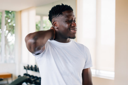 Fit African American man in white t-shirt holding sore neck and grimacing from pain on blurred gym background. Sportsman suffering from neck pain