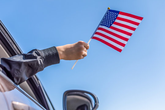 Boy holding Flag of America from the open car window on the sky background. USA.Concept