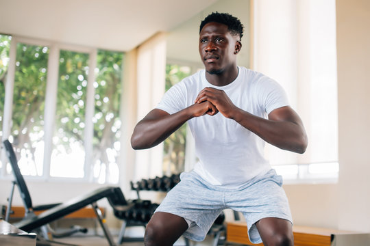 Concentrated fit African American man in sportswear warming up and doing squat exercise during workout. Young sportsman squatting in gym