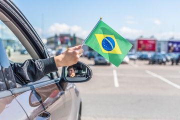 Boy holding Flag of Brazil from the open car window on the parking of the shopping mall. Concept Wall mural