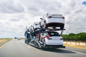 May 25, 2018 Bakersfield / CA / USA - Car transporter carries Tesla Model 3 new vehicles along the highway, back view of the trailer