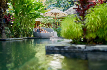 Candid shot of young caucasian couple lounging in modern chair near luxurious pool of tropical hotel and spa in Bali