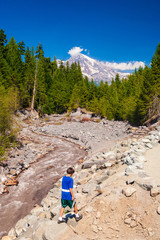 Fototapete - Young teenage boy playing along muddy river flowing from melting snow covered Mt. Rainier in the background.