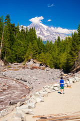 Wall Mural - Young teenage boy playing along muddy river flowing from melting snow covered Mt. Rainier in the background.