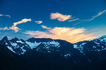 Wall Mural - Alpenglow on clouds over a rugged mountain range in Mt. Rainier National Park.