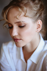 Young blonde woman in a casual white shirt and jeans in a loft interior, close up fashion portrait