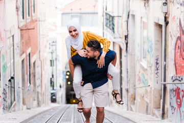 Smiling man carrying woman on back up steep street, Lisbon
