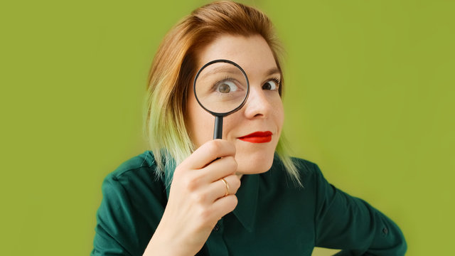 Search. A young woman with a magnifying glass searches, investigates and studies.