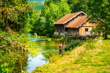 Angler an alter Mühle im Dessoubre im Jura