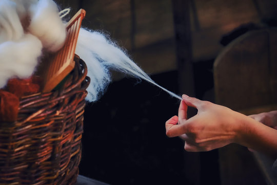 A woman's hand pulls yarn from a wicker basket. Spinner creates a thread of white wool.