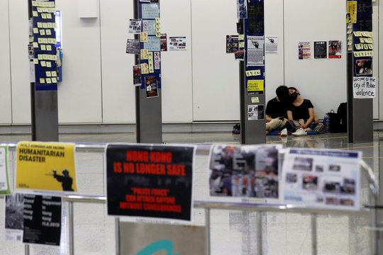 Anti-Extradition bill protesters couple sleep at arrival hall during a mass demonstration at the Hong Kong international airport, in Hong Kong
