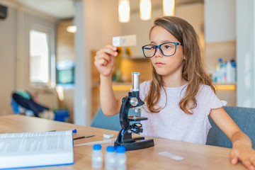 Preschool age girl looks into microscope. Child playing science in the kitchen at home. Cute little girl looking through the microscope. Little girl uses microscope